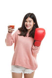 Young Asian woman with tomato juice and boxing glove. Stock Images