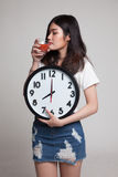 Young Asian woman with tomato juice and clock. Stock Image
