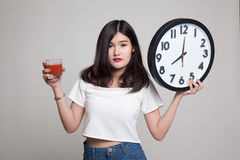 Young Asian woman with tomato juice and clock. Royalty Free Stock Photography
