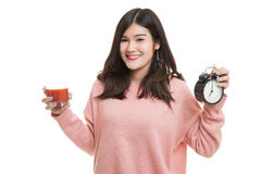 Young Asian woman with tomato juice and clock. Royalty Free Stock Images