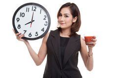 Young Asian woman with tomato juice and clock. Royalty Free Stock Photos
