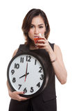 Young Asian woman with tomato juice and clock. Stock Photo