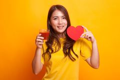 Young Asian woman with tomato juice and red heart in yellow dres. S on yellow background Royalty Free Stock Image