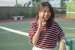 Young asian woman toothy smiling with happiness emotion speaking. On mobile phone outdoor ,looking sporty women Royalty Free Stock Photography