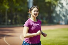 Young asian woman training outdoors. Young asian female athlete running training on track outdoors Stock Photography