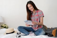 Young asian woman traveler holding map while sitting on bed with Royalty Free Stock Photo