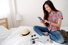 Young asian woman traveler holding map and smartphone while sitting on bed with smiling face, template, travel summer holiday royalty free stock photo