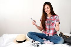 Young asian woman traveler holding map and  thumb upwhile sitting on bed with smiling face, template, travel summer holiday royalty free stock photography