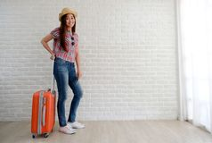 Young asian woman traveler holding smart phone and  luggage in white room with copy space, people summer holiday vacation royalty free stock photography