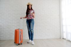 Young asian woman traveler holding smart phone and  luggage in white room with copy space, people summer holiday vacation stock photography