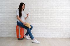 Young asian woman traveler holding smart phone and  sitting on luggage in white room with copy space, people summer holiday stock photo