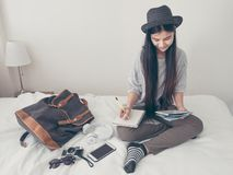 Young asian woman traveller planning vacation holiday expedition. On bed.preparing to travel.freedom wanderlust lifestyle stock photography