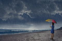 Young asian woman with umbrella looking at ocean view stock photography
