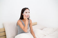 Young asian woman use of the facial mask on bed. Young asian woman use of the facial mask and sitting on bed stock images