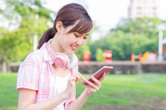 Young asian woman use phone. Young asian woman use the phone with earphones while walking stock images