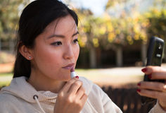 Young asian woman uses mobile phone as a mirror Stock Photography