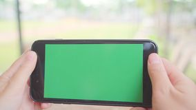 Young asian woman using black mobile phone device with green screen. Asian woman holding smartphone, scrolling pages in cafe. stock footage