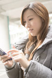 Young Asian woman using cellphone Stock Image