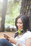 Young asian woman using a cellphone while sitting on the park Stock Photos