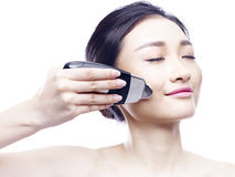 Young asian woman using a face spa device Stock Images