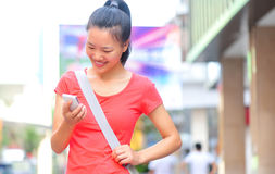 Young asian woman using her smart phone outdoor Royalty Free Stock Images