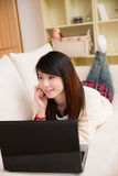 Young asian woman using a laptop and cellphone Stock Photography