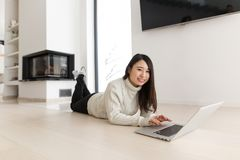 Young Asian woman using laptop on the floor. Young Asian woman using laptop in front of fireplace on cold winter day at home Royalty Free Stock Photos