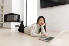 Young Asian woman using laptop on the floor. Young Asian woman using laptop in front of fireplace on cold winter day at home Stock Photos