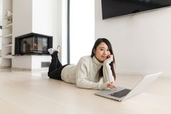 Young Asian woman using laptop on the floor. Young Asian woman using laptop in front of fireplace on cold winter day at home Royalty Free Stock Image