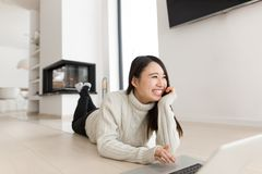 Young Asian woman using laptop on the floor. Young Asian woman using laptop in front of fireplace on cold winter day at home Stock Photo
