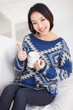 Young Asian woman using a pad PC and showing thumb. Young Asian woman using a pad PC and showing thumb in home background Royalty Free Stock Images