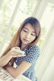 Young asian woman using smart phone in cafe Royalty Free Stock Image