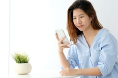 Young asian woman using smart phone with relax emotion on white. Background, people on phone, lifestyle Royalty Free Stock Images