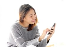 Young asian woman using smart phone with relax emotion on white. Background, people on phone, lifestyle Stock Images