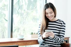 Young asian woman using smart phone while sitting by window cafe. Background, People technology and lifestyle Royalty Free Stock Photography