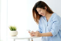 Young asian woman using smart phone with smiling, happy and relax emotion in white room background, people on phone, lifestyle stock image