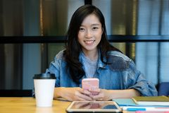 Young asian woman using smart phone while working at her office desk, working at home, casual office life concept stock photography