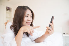 Young asian woman using smartphone on the bed Stock Photos
