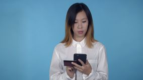 Beautiful korean female shopping use internet. Young asian woman using smartphone for buying online or pay order or bills on blue background in studio stock video footage