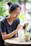 Young Asian woman  using smartphone in garden Stock Images