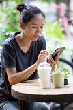 Young Asian woman  using smartphone in garden Stock Image