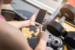 Young asian woman using smartphone in gym Royalty Free Stock Photos