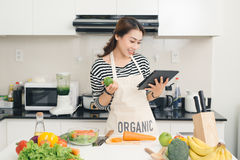 Young asian woman using a tablet computer to cook in her kitchen Royalty Free Stock Image