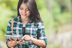Young asian woman using a tablet pc while walking on the park Stock Images