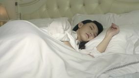 Young asian woman waking up in bed. With white bedding stock video footage