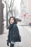 Young Asian woman walking on street. Young Asian woman walking on a winter city Royalty Free Stock Photo