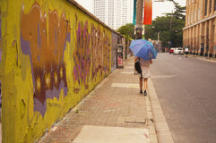 Young Asian woman walking with umbrella. A young Asian woman walking with an umbrella next to a graffiti covered wall in Shanghai China's M50 art district Stock Images