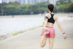 Young asian woman warming up before running stock photography
