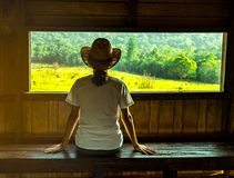Young Asian woman wear the hat sit on wooden bench and watching beautiful view of green grass field and forest. At wildlife observation tower in the evening Royalty Free Stock Image