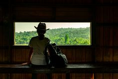 Young Asian woman wear the hat sit on wooden bench and watching beautiful view of tropical forest at wildlife observation tower Stock Photography